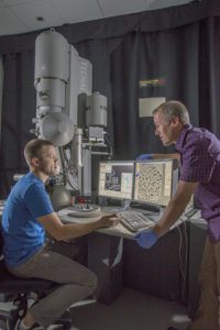 Two men talking to each other in front of a microscope